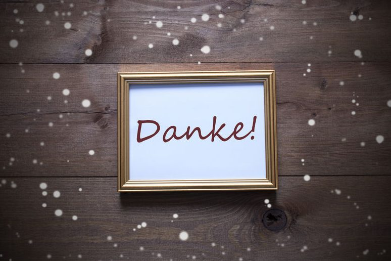 48143751 - one golden picture frame on wooden background. german text danke means thank you. rutic vintage or retro style. snowflakes for christmas or winter atmosphere. card for seasons greetings